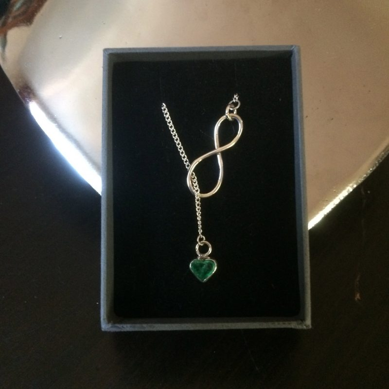 Emerald and silver necklace with an infinity clasp